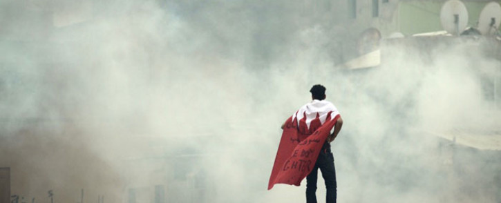 FILE: A photo taken on 31 March 2012 shows a Bahraini demonstrator drapped the Bahrain flag as smoke rises from tear gas fired by riot police during a protest on the southern outskirts of Manama. Picture: AFP