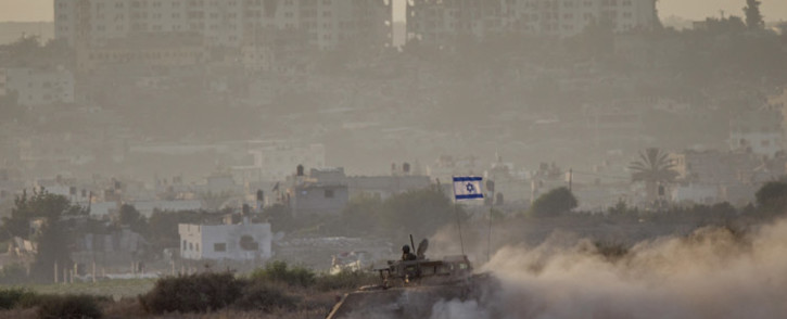 An Israeli army armoured personnel carrier (APC) rolls along Israel's border with the Hamas-controlled Gaza Strip on 4 August, 2014. Picture: AFP.