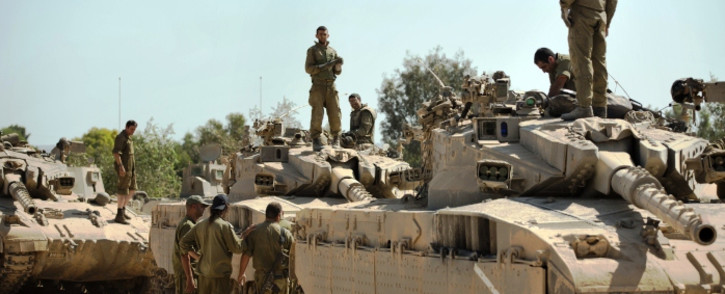 Israeli soldiers work on their Merkava tanks at an army deployment point near the Israeli-Gaza border on 20 August,2014. Picture:AFP.