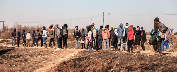 People outside Chris Hani Crossing Mall in Vosloorus, waiting for police to leave the area after looting on 14 July 2021. South Africa has been battling looting and riots since Saturday. Picture: Abigail Javier/Eyewitness News