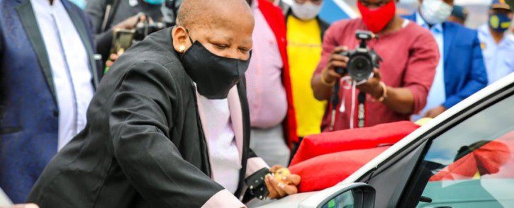 Transport Deputy Minister Dikeledi Magadzi performs the ceremonial ritual of cutting the ribbon for the 31 law enforcement vehicles handed over to the North West Province on 29 March 2021. Picture: @Dotransport/Twitter.