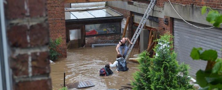 This photograph taken on July 15, 2021 shows a Belgian family being helped to safety after their house was engulfed by floodwaters from the river Vesdre in Trooz. Picture: AFP.