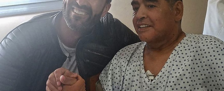 This handout photo released by the press officer of Diego Armando Maradona shows Argentine football legend Diego Maradona (R) shaking hands with his doctor Leopoldo Luque in Olivos, Buenos Aires province, Argentina, on 11 November 2020. Picture: AFP