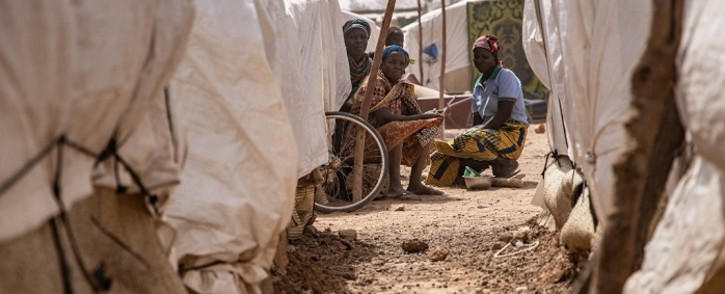 Women sit outside their shelter, in camp for internally displaced people in Barsalogho, on 27 January 2020. Picture: AFP