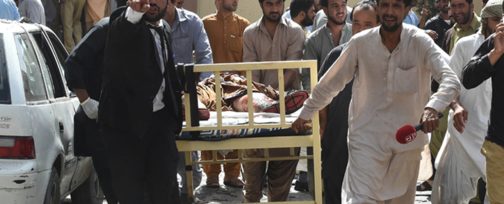 Pakistani lawyers and local media personnel carry a bed to move the body of a news cameraman after a bomb explosion at a government hospital premises in Quetta on 8 August, 2016. Picture: AFP.
