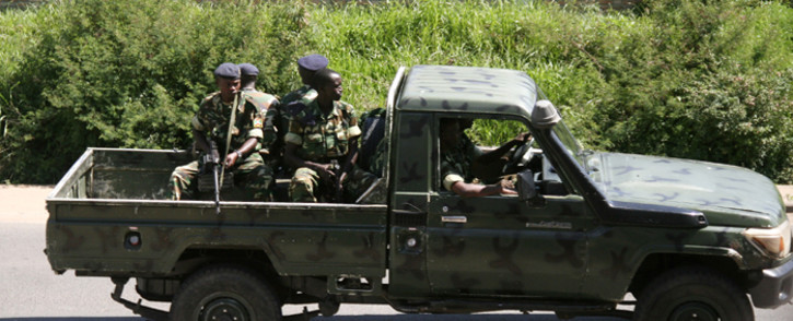 Military personnel sits aboard a vehicle driving through the Musaga neighbourhood of the city of Bujumbura on December 11, 2015. Heavily-armed gunmen launched coordinated assaults on three army barracks in the Burundian capital on December 11 leaving at least a dozen dead in the worst unrest since a failed May coup. Picture: AFP.