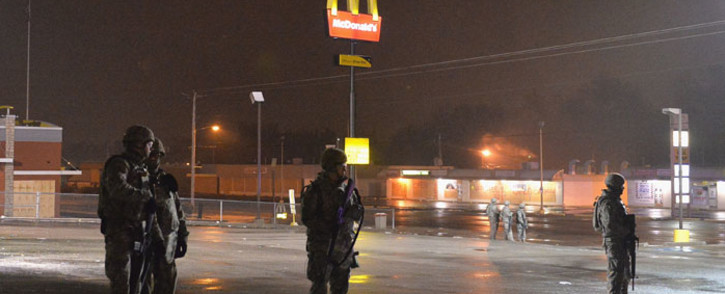 Members of the Missouri National Guard stand on patrol on West Florissant Avenue on 26 November 2014 in Ferguson, Missouri. Picture: AFP.
