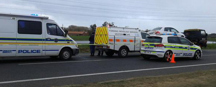 Police officials and forensic experts leave the scene where a police officer was attacked and stabbed to death while on his way to work on the N2 on 29 July 2015. Picture: SAPS.