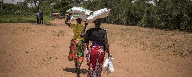 FILE: Two women walk away from a food distribution carrying bags of beans and maize meal in Simumbwe on 22 January 2020. Funding is desperately needed to meet the needs of the 2.3 million severely food insecure people in Zambia. Picture: AFP.