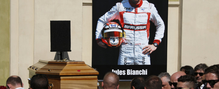 Pallbearers carry the coffin of French Formula One driver Jules Bianchi past a portrait of him during his funeral ceremony at the Cathedrale Sainte Reparate in Nice, southeastern France, on 21 July, 2015. Picture: AFP.
