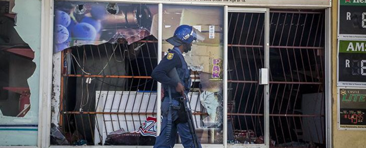 FILE: A police officer walks outside a looted liquor store in Coligny after protests in the town on 25 April 2017 over the death of a young boy. Picture: Reinart Toerien/EWN
