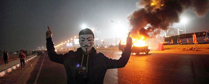 FILE: A man stands near a burning car outside a sports stadium in a Cairo's northeast district during clashes between supporters of Zamalek football club and security forces on 8 February 2015. 14 people were killed and several injured. Picture: AFP.