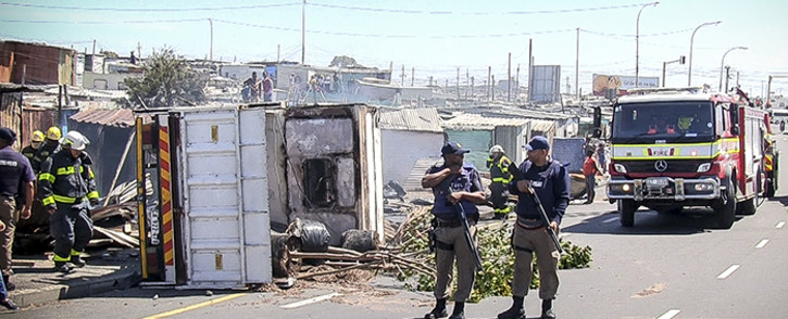 FILE:Police stand guard over firecrews that were busy dousing the truck and shack that burnt during protests in Khayelitsha over illegal electricity connections. Picture: Thomas Holder/EWN