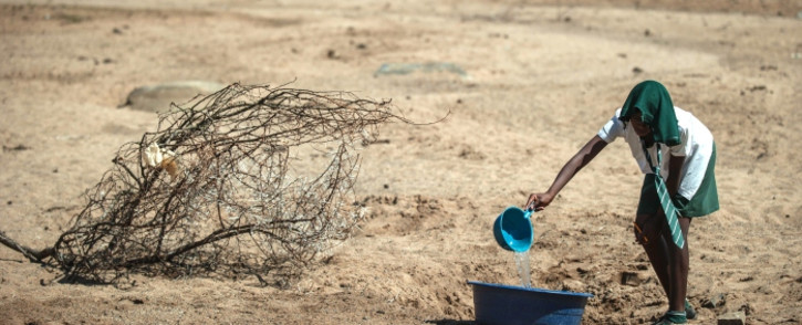 FILE: A school girl tries to collect water from a dry puddle in Nongoma, in KwaZulu-Natal, which has been badly affected by the recent drought. Picture: AFP.