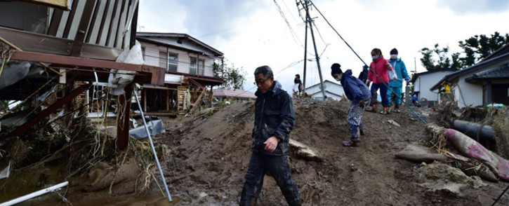 Residents walk past mud and flood-damaged homes in Nagano on 15 October 2019, after Typhoon Hagibis hit Japan on 12 October 2019. Picture: AFP