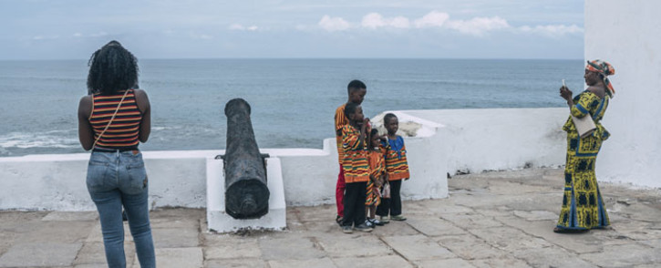 """Tourists pose for pictures at the Cape Coast Castle on 18 August 2019. African-American visitors are flocking to Ghana as it marks the """"Year of Return"""" to remember the 400th anniversary of the first slave ship landing in Virginia. Picture: AFP"""