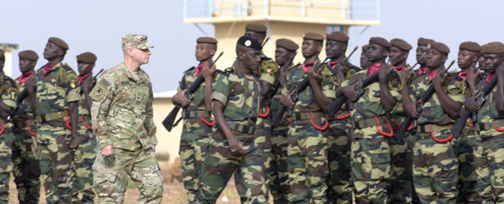 Senegals Army General Amadou Kane (C) and US Army General Donald Bolduc (L) review the troops during the inauguration of a military base in Thies, 70 km from Dakar, on 8 February 8 2016 on the second day of a three-week joint military exercise between African, US and European troops, known as Flintlock. Picture: Seyllou/AFP.