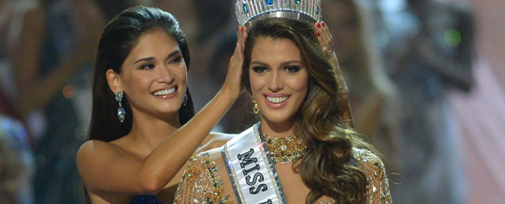Miss Universe contestant Iris Mittenaere (R) of France is crowned the new 2017 winner by former Miss Universe Pia Wurtzbach of the Philippines (L) during the Miss Universe pageant at the Mall of Asia Arena in Manila on 30 January 2017. Picture: AFP.