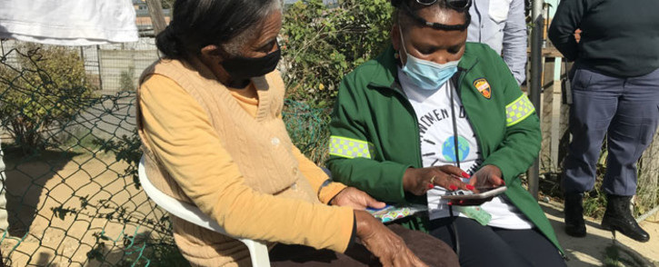 Western Cape Health MEC Nomafrench Mbombo (right) helps Paarl resident Spasie Daniels (84) register for the COVID-19 vaccine on 13 May 2021. Picture: Kevin Brandt/Eyewitness News