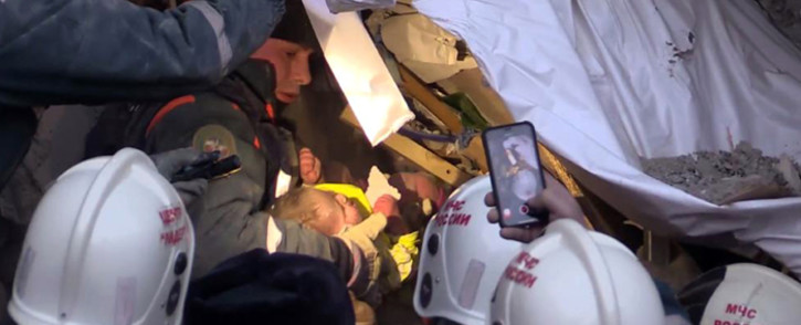 This handout picture released by The Russian Emergency Situations Ministry on 1 January 2019, shows emergency officers transporting a baby survivor after a gas explosion rocked a residential building in Russia's Urals city of Magnitogorsk. Picture: AFP.