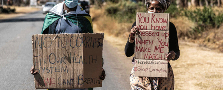 A man and a woman hold placards during an anti-corruption protest march along Borrowdale road, on 31 July 2020 in Harare. Picture: AFP
