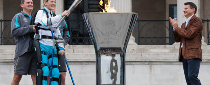 Chairman of LOCOG Lord Sebastian Coe, (R) applauds as British paralympic athlete Claire Lomas (2nd L) lights the Paralympic Cauldron in London's Trafalgar Square. The former chiropractor uses a bionic ReWalk suit. Picture: AFP.