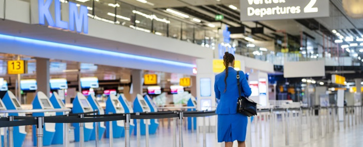 A KLM flight attendant walks in the Schiphol Airport, on January 21, 2021, as Dutch airline KLM logo is seen. Dutch airline KLM said on January 21 it will shed between 800 and 1,000 more jobs as the coronavirus pandemic is hitting the aviation sector for longer than expected. Picture: Evert Elzinga/ AFP.