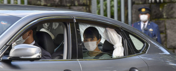 Japan's Princess Mako (C) leaves Akasaka Estate in Tokyo on 26 October 2021, to attend a press conference with her husband Kei Komuro. Picture: Kazuhiro NOGI/AFP