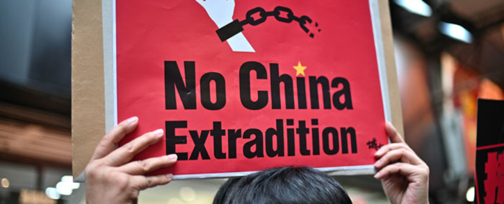 In this file photo taken on 28 April 2019, an activist holds a placard during a protest in Hong Kong against a controversial move by the government to allow extraditions to the Chinese mainland. Picture: AFP