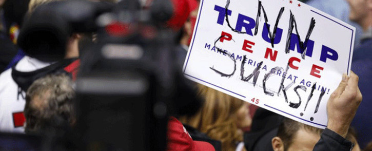 "A supporter of President Donald Trump holds up a sign reading ""CNN sucks"" during a campaign rally for Republican Senate candidate Mike Braun and attended by President Donald Trump at the County War Memorial Coliseum 5 November, 2018 in Fort Wayne, Indiana. Picture: AFP"
