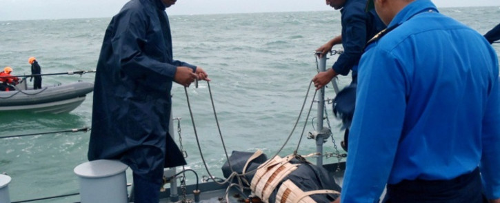This handout photo made available on December 31, 2014 by Malaysias Ministry of Defence shows Royal Malaysian Navy search and rescue crews retrieving a victim from AirAsia flight QZ8501 during their search and rescue operations in Indonesias Java Sea. Picture: AFP/Malaysian Royal Navy.
