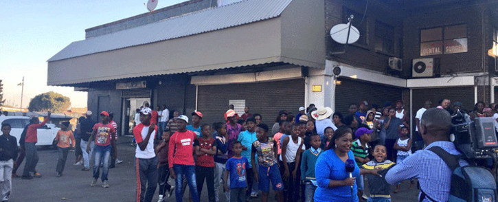 A group of White City residents gathers near a news crew after some of the stores have been looted and two people killed. Picture: Katleho Sekhotho/EWN.