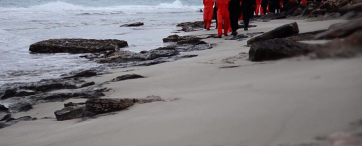An image grab taken from a video released by the jihadist media arm Al-Hayat Media Centre on 15 February, 2015 purportedly shows black-clad Islamic State (IS) group fighters leading handcuffed hostages, said to be Egyptian Coptic Christians, wearing orange jumpsuits before their alleged decapitation on a seashore in the Libyan capital of Tripoli. Picture: AFP