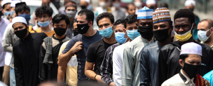 Muslim worshipers, mask-clad due to the COVID-19 coronavirus pandemic, wait outside the historic al-Azhar mosque in the centre of Islamic Cairo as they arrive to perform the Friday prayers under new pandemic restrictions, in Egypt's capital on 28 August 2020. Picture: AFP.