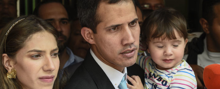 """Opposition leader and self-proclaimed """"acting president"""" Juan Guaido (C) addresses the press as he holds his daughter Miranda, next to his wife Fabiana Rosales (L), outside his home in Santa Fe, Caracas on 31 January 2019. Picture: AFP"""
