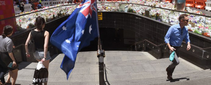 FILE: Commuters use a stairway to a rail station near floral tributes left in Sydney's Martin place, one week after a siege at the Lindt cafe which saw two hostages and the gunman killed, on 22 December, 2014. Picture: AFP.