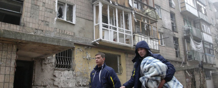 Local people walk past damaged buildings after overnight shelling in Donetsk, Ukraine. A new wave of violence was reported although a cease-fire was declared in the main separatists city. Picture: EPA.