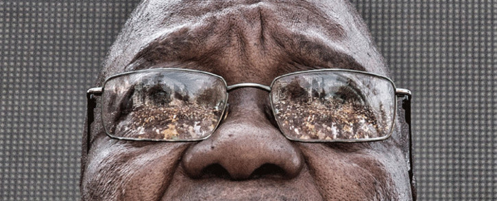 The crowd who gathered to support former President Jacob Zuma is seen reflected in his glasses as he waits to speak after appearing on corruption charges at the Durban High Court on 6 April 2018. Picture: Ihsaan Haffejee/Eyewitness News.