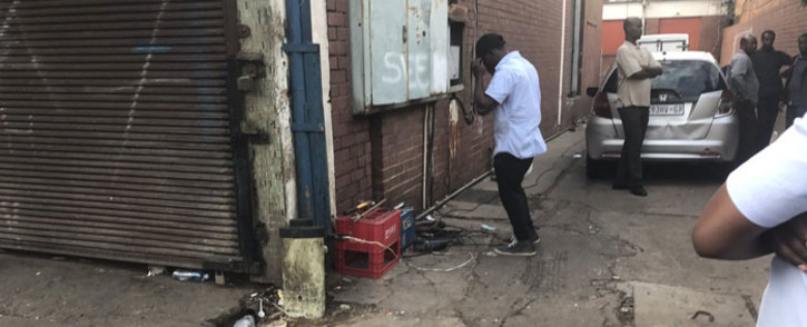 Foreign nationals in Pretoria CBD fix and weld their gate, saying they will hide inside to protect their shops and stock after a day of protests. Picture: Clement Manyathela/EWN.