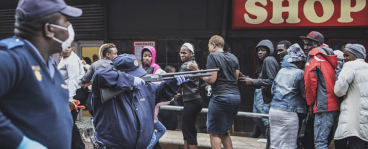A South African policeman points his pump rifle to disperse a crowd of shoppers in Yeoville, Johannesburg, on 28 March 2020 while trying to enforce a safety distance outside a supermarket amid concern of the spread of COVID-19 coronavirus. Picture: AFP