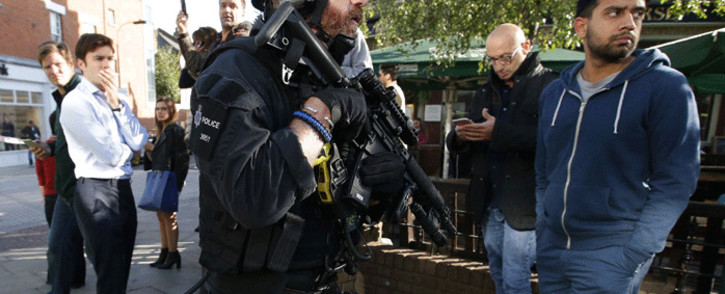 Armed British police officers stand on duty outside Parsons Green underground tube station in west London on 15 September 2017. Picture: AFP.