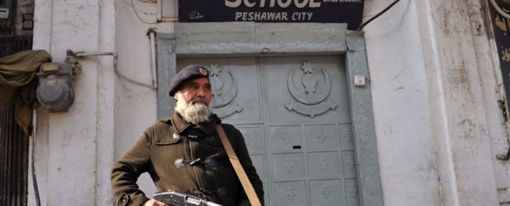 A Pakistani policeman stands guard in front of a school a day after militant attack on Bacha Khan University in Peshawar on January 21, 2016. Pakistan observed a day of national mourning on January 21 for 21 people killed when heavily armed gunmen stormed a university in the troubled northwest, exposing the failings in a national crackdown on extremism. Picture: AFP.