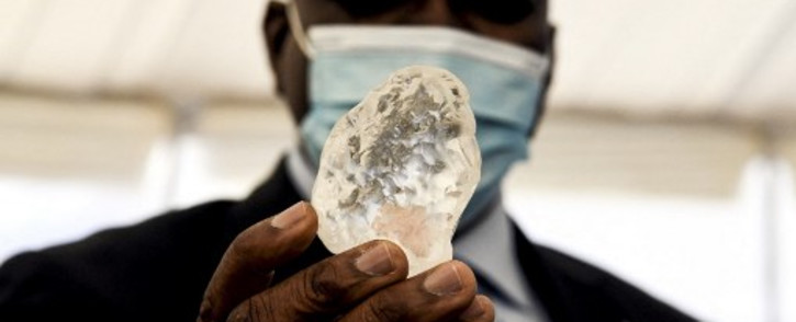Botswana President Mokgweetsi Masisi (R) holds a gem diamond in Gaborone, Botswana, on 16 June 2021. Botswanan diamond firm Debswana said on 16 June 2021 it had unearthed a 1,098-carat stone that it described as the third largest of its kind in the world. The stone, found on 1 June 2021 was shown to President Mokgweetsi Masisi in the capital Gaborone. Picture: AFP