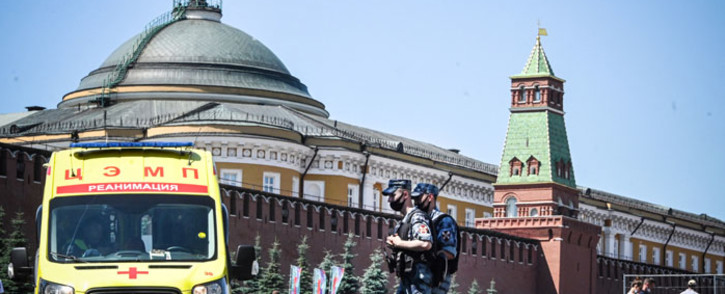 FILE: Russian National Guard servicemen wearing face masks walk along Red Square past an ambulance in central Moscow on 18 June 2021. Picture: Alexander NEMENOV/AFP