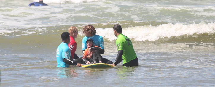 A young surfer gets a push on a longboard as volunteers teach him how to surf. Picture: Bertram Malgas/EWN.