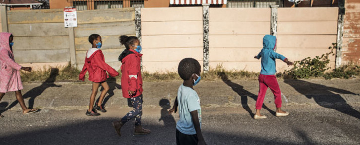 """FILE: Children wearing protective facemasks and extending their arms to enforce social distancing, walk with volunteers of the non-profit organisation and charity group """"Hunger has no Religion"""" in Westbury, Johannesburg, on 23 May 2020. Picture: AFP"""