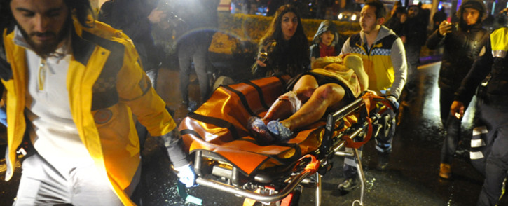 First aid officers carry an injured woman at the site of an armed attack on 1 January, 2017 in Istanbul. Picture: AFP.