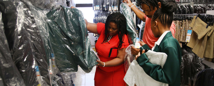 A mother helps her young daughter choose the right blazer size as schools across the country reopen for the 2019 academic year. Photo: Bertram Malgas