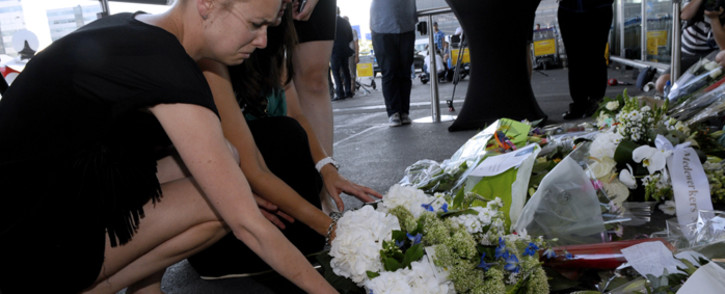 People lay flowers and light candles in front of the Schiphol airport on July 18, 2014, a day after a Malaysian Airlines flight MH17 carrying 298 people from Amsterdam to Kuala Lumpur crashed in eastern Ukraine. Picture: AFP.