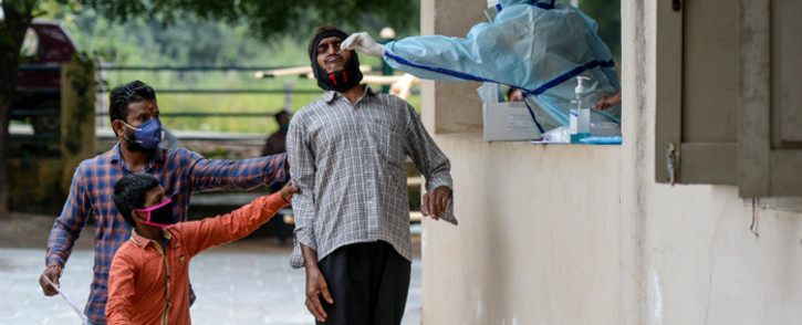 Residents hold a man as a health worker collects a swab sample from him to test for the COVID-19 coronavirus at a community gym centre on the outskirts of Hyderabad, India, on 8 October 2020. Picture: AFP.